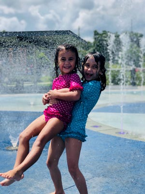 Daughters, Viv, 4 and Apollonia, 6, enjoy  time at the splash pad at Cascades Park.