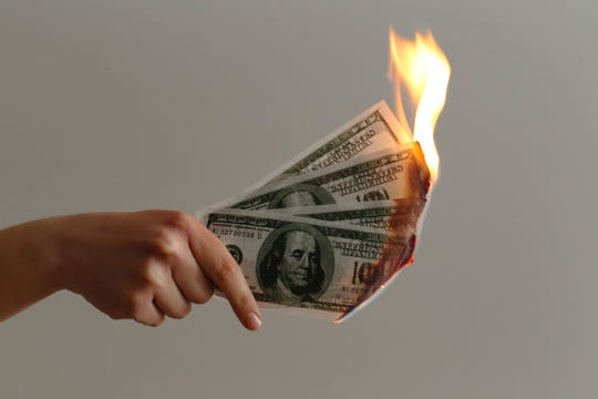 A woman holds burning cash.