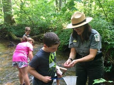 A park ranger shows an item to a young boy while exploring a creek at Paris Mountain State Park.