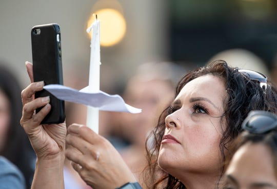 Jessica Marquez-Zepeda and other community members gather Monday, July 29, 2019 next to Gilroy's library to honor victims of Sunday's shooting at the Gilroy Garlic Festival.