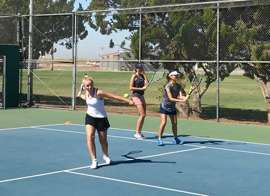 Campbell Todd, 14, Mika Temmerman, 15, and Hanbin Yu, 15, practice tennis strokes at Plaza Park on July 29, 2019.