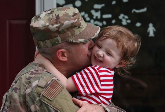 James Friedlander, a member of the Air National Guard, hugs his 2-year old daughter Vivian, after returning from a 6-month deployment in Qatar July 29, 2019. Friedlander, who is also a firefighter with the FDNY and Brewster Fire Department, was treated to a surprise as a parade of fire apparatus welcomed him to his Brewster home.