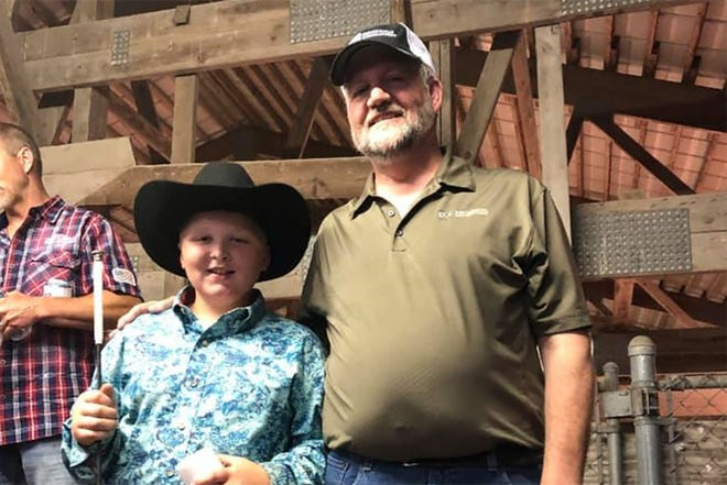 4-H exhibitor Mason Gorecki (left) sells his 246-pound pig to Joe Pues of EGI Mechanical and donates all proceeds to the Diemel family.