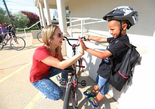 Courtney King, of West Des Moines, ESL teacher at Jensen Elementary School, left, hi-fives Jaylon Gulling, 7, of Urbandale, during the national Bike To School Day at Jensen Elementary School on Wednesday, May 7, 2014.