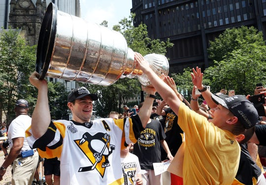 Chris Kunitz holds the Stanley Cup out for fans to touch during the 2017 Stanley Cup championship parade and rally.