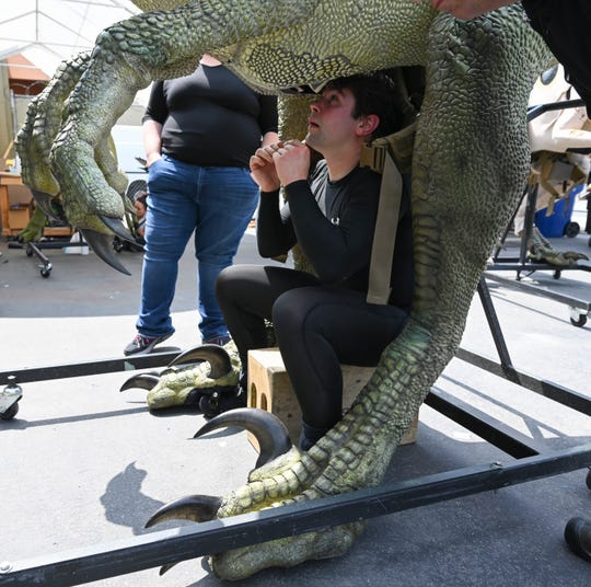 "Robert Gardner bears the weight of a velociraptor in an attached backpack while operating the dinosaur in the ""Jurassic World Live Tour."""