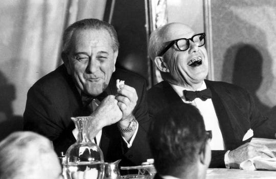 In this Nov. 9, 1967, file photo, U.S. President Lyndon B. Johnson, left, munching on a cookie, and George Meany, president of the AFL-CIO, laugh at a speaker's remark during the first annual Jewish Labor Committee Human Rights Awards dinner at the Sheraton in New York City.