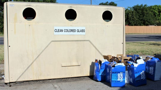 Before glass no longer is accepted as a recyclable item, someone left several containers of empty beer bottles at the glass container at the H-E-B neighborhood recycling center.