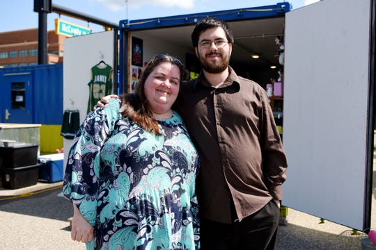 """Christy Cooper and her son Bret Hook pose for a portrait together at BC Cargo in front of the trailer they once sold customized memorabilia out of on Tuesday, July 30, 2019 in Battle Creek, Mich. In 2015, Bret left home to join the Navy, so Christy and her husband made dog tags with his picture on them, an idea that evolved into their business """"Totally Memories."""""""