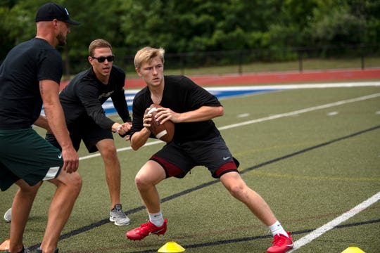 Ryan Van Dyke and Danny Welke provide personal quarterback training to Marshall senior Codey Shellenberger on Wednesday, July 31, 2019 at Harper Creek High School.