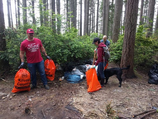 Volunteers gather bags of garbage during Northwest Hospitality's cleanup of an area in Bremerton. The organization has removed over 16,340 pounds of garbage from public areas in Washington since it was founded in 2016.