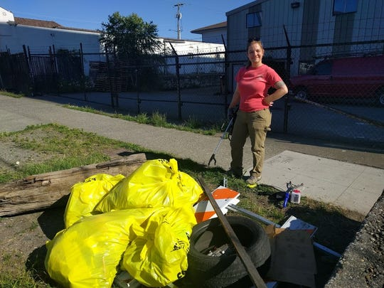 A Northwest Hospitality volunteer stands near her pile of gathered garbage after a cleanup in King County in April.