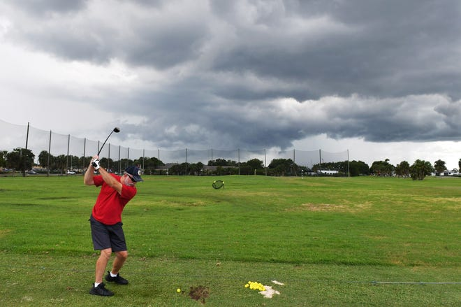 Melbourne resident Dale Foster takes a few practice swings as a storm approaches at Mallards Landing Golf Course in this file photo.