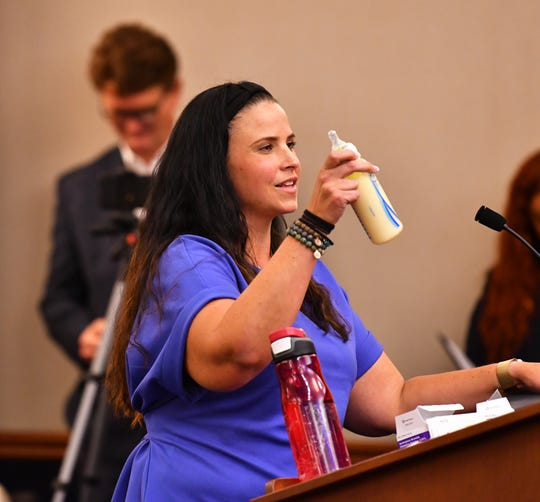Nancy Kirby holds up a bottle of formula made with city water, says that it smells. It was a packed city council chamber with 219 people in the meeting and people waiting to get in for the meeting on the water quality of Melbourne's drinking water.