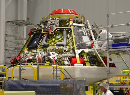 Inside the Boeing facility at Kennedy Space Center, engineers and technicians in the high bay prepare the crew module for the upcoming orbital flight test.