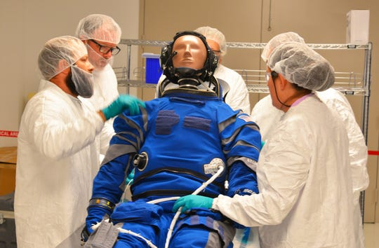 Inside the Boeing facility at Kennedy Space Center, engineers and technicians fit the the anthropometric test device- the test dummy- into a space suit. The test dummy will fly on the orbital flight test of the CST-100 Starliner.