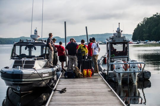 Members of the Vermont State Police, Colchester Police and Colchester Technical Rescue wait to be deployed on a dock in Colchester, VT, July 31, 2019.