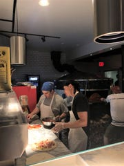 Pizzas go from balls of dough to finished at Pizzeria Verita's open kitchen on July 30, 2019.