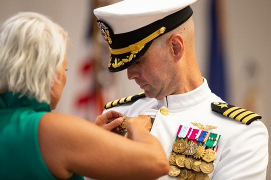 New commanding officer Capt. Christopher Jason has his command pin given to him by his wife, Cheryl, during the the change of command ceremony at Naval Air Station Corpus Christi on Wednesday, July 31, 2019.