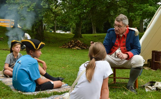 A member of the Joseph Ogle Company speaks with a Liberty Camp group about how to make a fire and living conditions during the Revolutionary War.