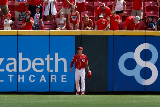 Cincinnati Reds right fielder Michael Lorenzen (21) smiles after making a leaping catch at the warning track in the ninth inning of the MLB National League game between the Cincinnati Reds and the Pittsburgh Pirates at Great American Ball Park in downtown Cincinnati on Wednesday, July 31, 2019. The Reds won 4-1.
