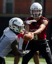 Cincinnati Bearcats quarterback Desmond Ridder (9) hands the ball off to Cincinnati Bearcats running back Michael Warren II (3) during Cincinnati Bearcats football practice Wednesday, July 31, 2019, at the University of Cincinnati.