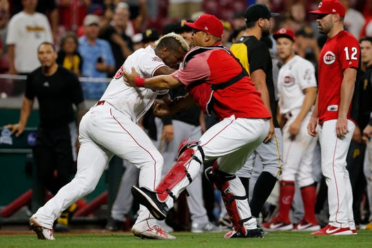Cincinnati Reds right fielder Yasiel Puig (66) charges the Pittsburgh Pirates dugout again as a brawl disperses in the ninth inning of the MLB National League game between the Cincinnati Reds and the Pittsburgh Pirates at Great American Ball Park in downtown Cincinnati on Tuesday, July 30, 2019. The Pirates won 11-4.
