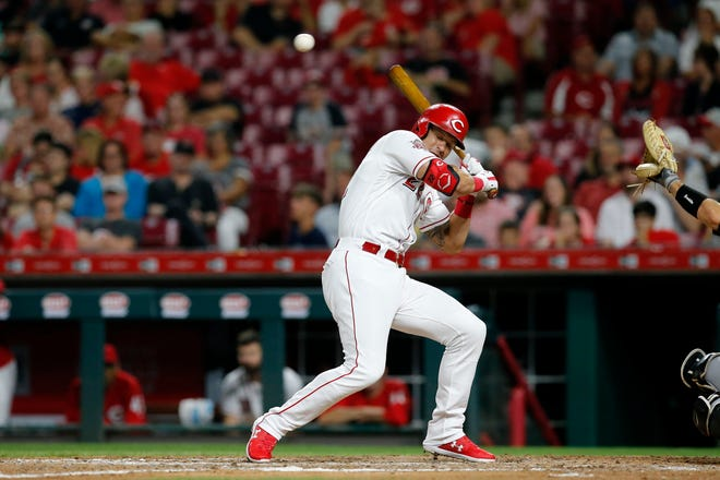A wild pitch flies over the head of Cincinnati Reds second baseman Derek Dietrich (22) as he comes to bat for the first time in the seventh inning of the MLB National League game between the Cincinnati Reds and the Pittsburgh Pirates at Great American Ball Park in downtown Cincinnati on Tuesday, July 30, 2019. The Pirates won 11-4.