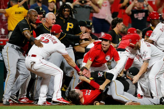 Cincinnati Reds manager David Bell (25) is pushed to the bottom of a scrum as the Cincinnati Reds and Pittsburgh Pirates brawl in the ninth inning of the MLB National League game between the Cincinnati Reds and the Pittsburgh Pirates at Great American Ball Park in downtown Cincinnati on Tuesday, July 30, 2019. The Pirates won 11-4.