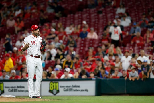 Cincinnati Reds first baseman Joey Votto (19) shouts at the Pirates dugout between innings following a pitch over the head of second baseman Derek Dietrich (22) in the eighth inning of the MLB National League game between the Cincinnati Reds and the Pittsburgh Pirates at Great American Ball Park in downtown Cincinnati on Tuesday, July 30, 2019. The Pirates won 11-4.