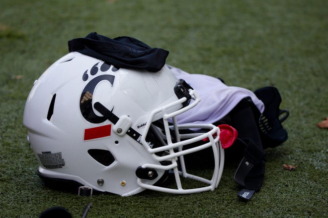 A Cincinnati Bearcats helmet and gloves sits on the turf during Cincinnati Bearcats football practice Wednesday, July 31, 2019, at the University of Cincinnati.