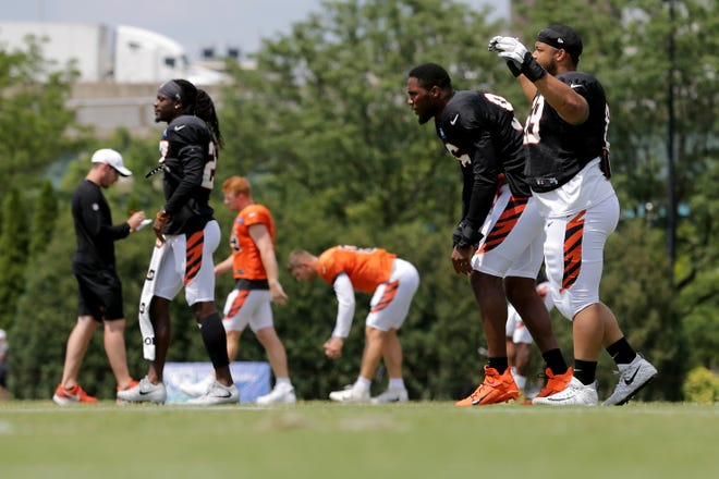 Cincinnati Bengals nose tackle Niles Scott (69), far right, stretches with Cincinnati Bengals defensive end Carlos Dunlap (96) and Cincinnati Bengals cornerback Dre Kirkpatrick (27) during Cincinnati Bengals training camp practice, Wednesday, July 31, 2019, at the practice fields next to Paul Brown Stadium in Cincinnati.