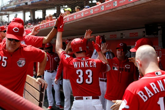 Cincinnati Reds left fielder Jesse Winker (33) celebrates in the dugout after hitting a solo home run in the first inning of the MLB National League game between the Cincinnati Reds and the Pittsburgh Pirates at Great American Ball Park in downtown Cincinnati on Wednesday, July 31, 2019. The Reds led 3-0 after three innings.