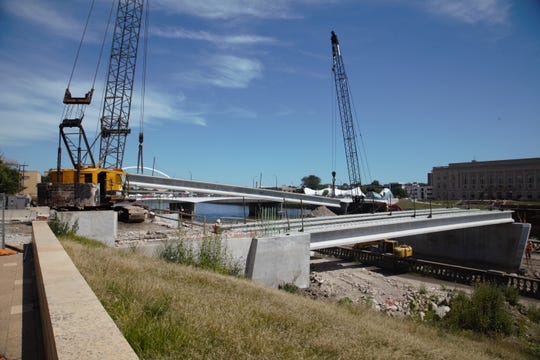 Workers on Tuesday, July 30, 2019, installed the first support beams for the Locust Street bridge in downtown Des Moines. The project was delayed by high water, which will push back its opening until next summer.