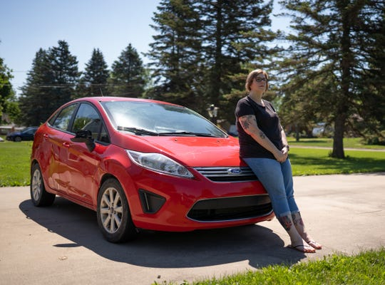 Michelle Hughes sits on her 2012 Ford Fiesta parked at her home in Flint on Wednesday, June 26, 2019.