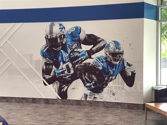 A mural in the Detroit Lions' Allen Park training facility shows ex-Lion Calvin Johnson and current Lion Kenny Golladay.