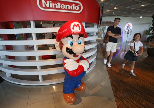 Japanese video game maker Nintendo Co. has reported fiscal first quarter profit dipped to about half of what it was the previous year despite improved sales as an unfavorable exchange rate eroded earnings.