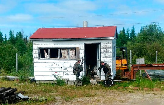 In this recent photo provided by the Royal Canadian Mounted Police, RCMP officers canvas homes and buildings in the Gillam, Manitoba area, as they continue to search for two teenagers being sought in the killings of three people in northern British Columbia.