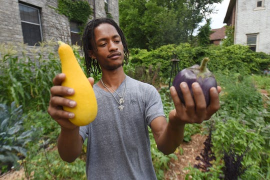 Dwight Roston, youth ambassador at Church of the Messiah, shows the vegetables he picked in the Detroit church's garden Wednesday in preparation for a food giveaway this weekend on the 13th Arise Detroit Neighborhoods Day.