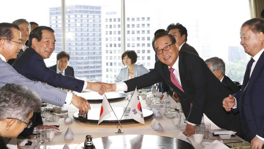 Japanese lawmaker Fukushiro Nukaga, second left, and South Korean counterpart Suh Chung-won, second from right, shake hands at a hotel during a meeting in Tokyo, Tuesday, July 31, 2019.