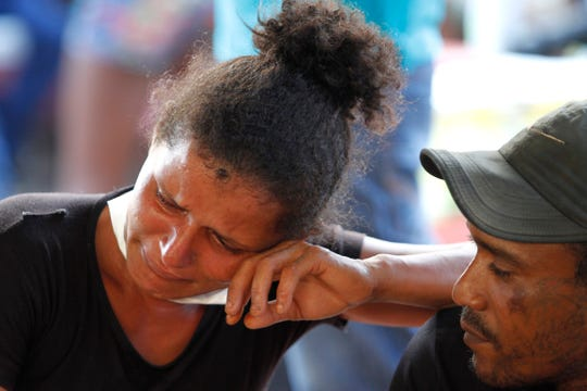 A woman cries as she waits outside the coroner's office in Altamira, Brazil, Tuesday.