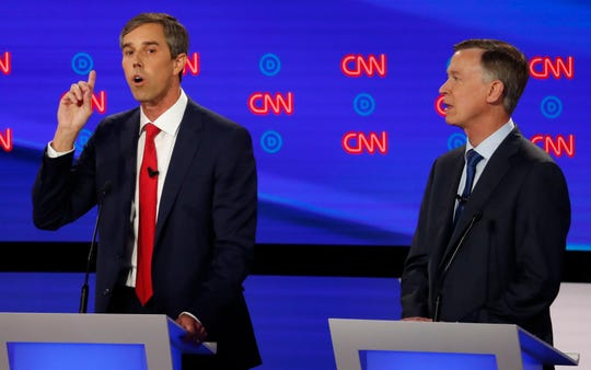 Former Texas Rep. Beto O'Rourke speaks as former Colorado Gov. John Hickenlooper listens during the first of two Democratic presidential primary debates hosted by CNN.