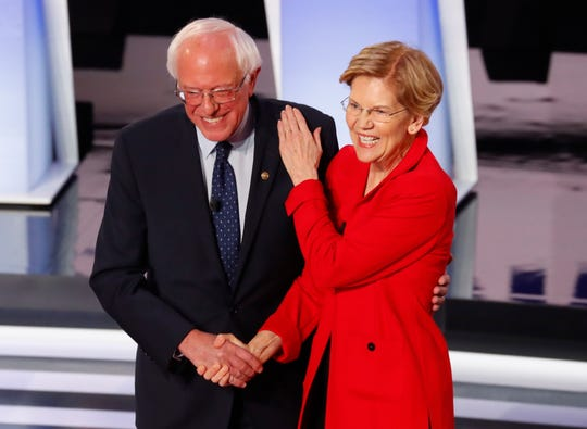 Sen. Bernie Sanders, I-Vt., and Sen. Elizabeth Warren, D-Mass., greet each other before the first of two Democratic presidential primary debates in Detroit.
