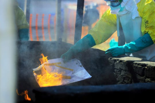 In this Saturday, July 20, 2019 photo, a health worker in protective clothing burns the college entry exam papers completed by Ebola patient Claude Mabowa Sasi, 21, after they were photographed for scoring in Beni, Congo.
