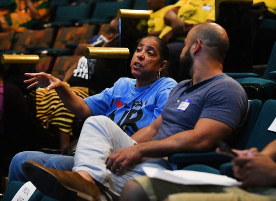 Theresa Landrum and Mero Gonzalez talk during a commercial break during a debate watch party at the Charles H. Wright Museum of African American History.