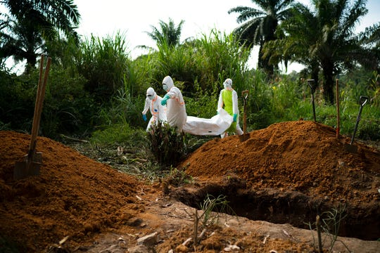 In this Sunday, July 14, 2019 photo, workers bury the remains of Mussa Kathembo, an Islamic scholar who had prayed over those who were sick in Beni, Congo. Kathembo himself died of Ebola.