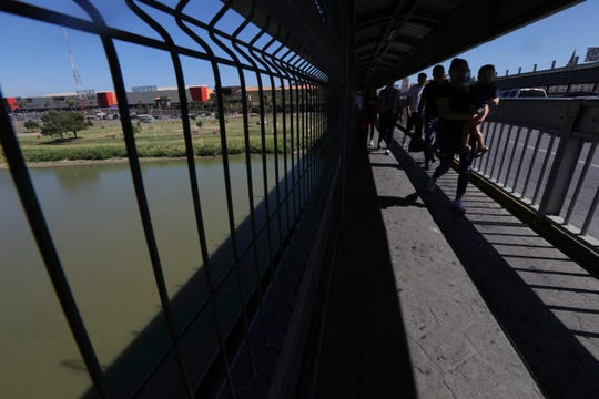 In this July 18, 2019, file photo, people walk back to Mexico on International Bridge 1 Las Americas, a legal port of entry which connects Laredo, Texas in the U.S. with Nuevo Laredo, Mexico.