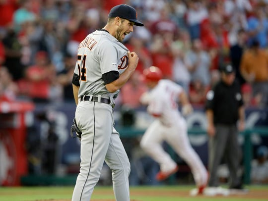 Detroit Tigers starting pitcher Drew VerHagen, left, reacts as Los Angeles Angels' Matt Thaiss rounds third after hitting a two-run home run during the second inning.
