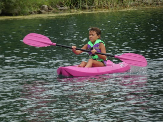 Bristol Westlick, 7, kayaks around a pond during a week-long camp at Camp Fire.