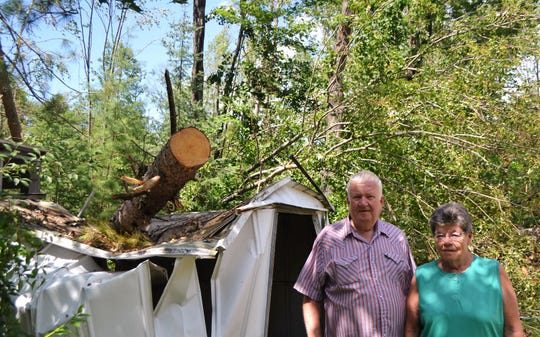 Ron and Judy Mangold stand next to a shed at their summer home in the town of Doty on Monday, July 29. Several trees struck their house, punching holes in the roof, and the July 19 storm downed at least 100 trees on their property.